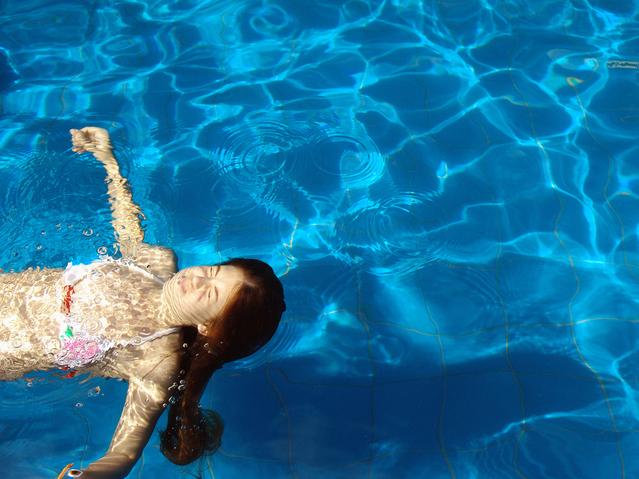 děvče plave v bazéně za slunečného dne